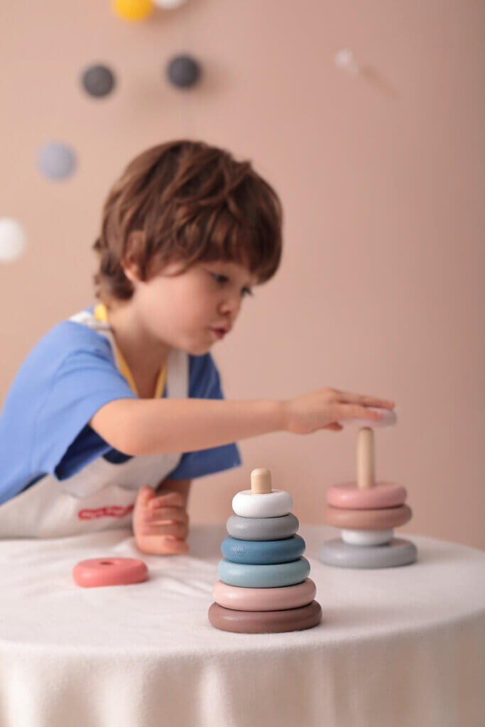 kid playing with stacking tower